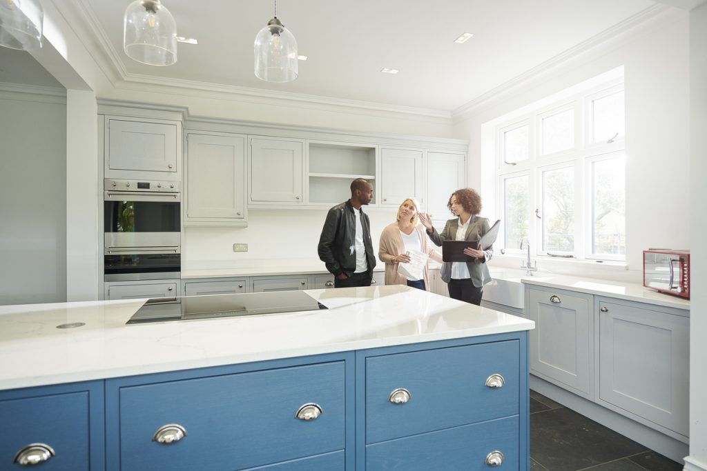 professional-appraiser-discussing-home-value-in-kitchen-with-couple-near-island-with-blue-cabinets