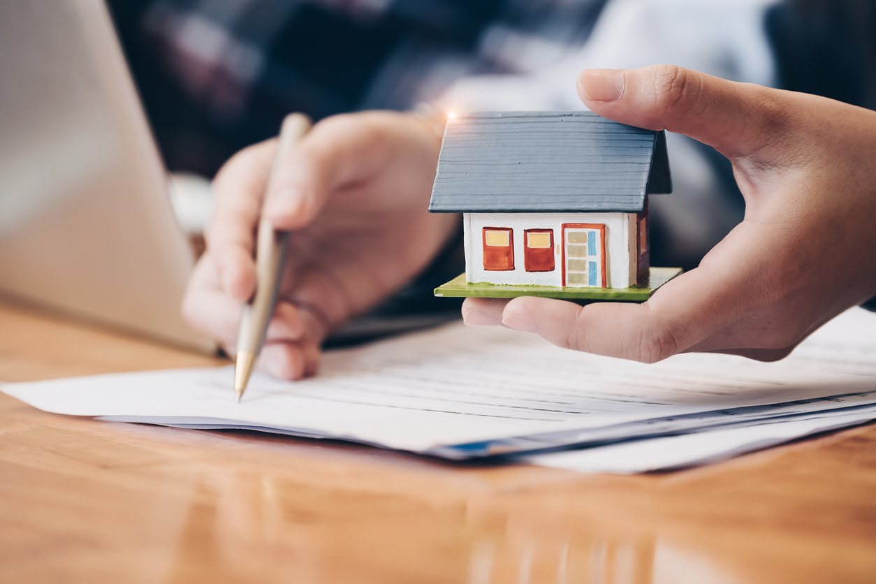 hand-holding-small-model-house-while-other-hand-holds-pencil-over-home-value-paperwork